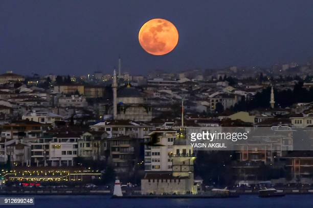 A picture taken on January 31 2018 shows the moon during a lunar eclipse referred to as the 'super blue blood moon' up in the sky above the Bosphorus...