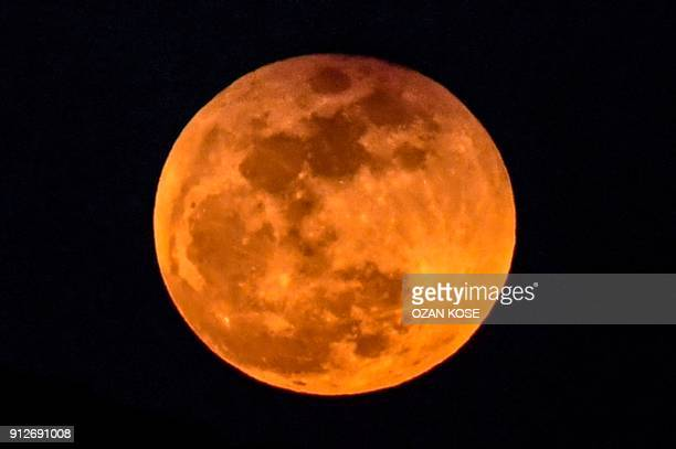 """Picture taken on January 31, 2018 shows the moon rising behind a mountain during a lunar eclipse, referred to as the """"super blue blood moon"""" near..."""