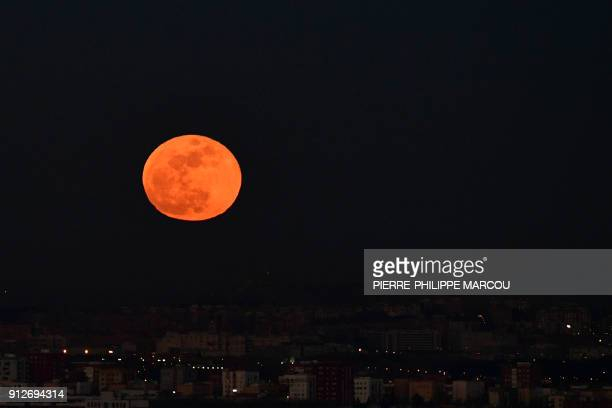A picture taken on January 31 2018 shows the moon rising over Madrid Stargazers across large swaths of the globe from the streets of Los Angeles to...