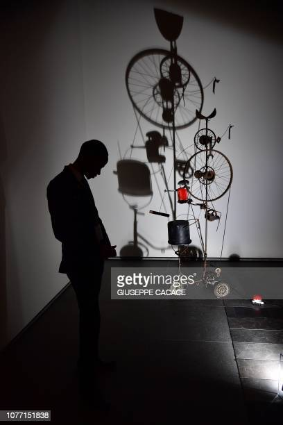 "Picture taken on January 4 shows a security guard next to a creation by Jean Tinguely titled "" Orange press ""a+b"" "" at the Louvre Museum in Abu Dhabi..."