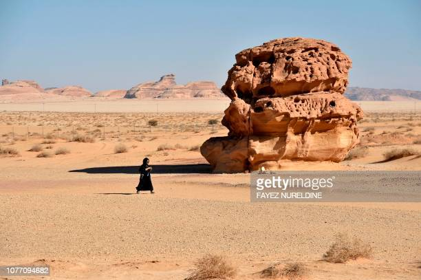 A picture taken on January 4 shows a woman walking past rosecoloured sandstone in Madain Saleh a UNESCO World Heritage site near Saudi Arabia's...