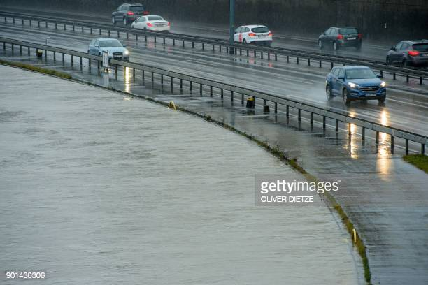 A picture taken on January 5 2018 shows cars driving past the Saar river whose water level has risen high due to heavy rains in Saarbrucken western...