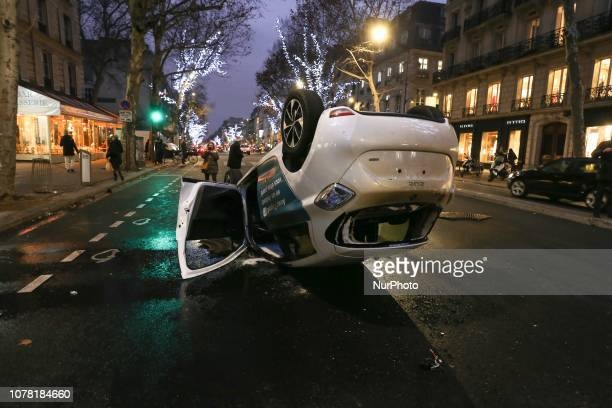 A picture taken on January 5 2019 at he SaintGermain boulevard in Paris shows a car overturned during a demonstration called by the yellow vests...