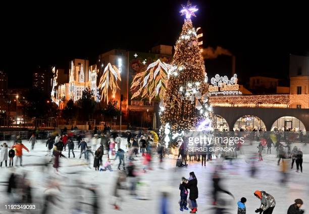 A picture taken on January 6 shows people skating around a christmas tree on an ice skating rink in Kiev during Orthodox Christmas Eve Orthodox...