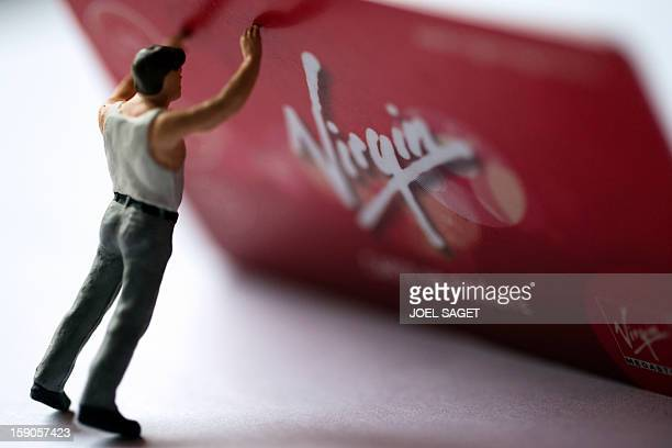 Picture taken on January 7 2013 in Paris shows an illustration made with a figurine holding a Virgin Megastore loyalty card The Virgin Megastore...