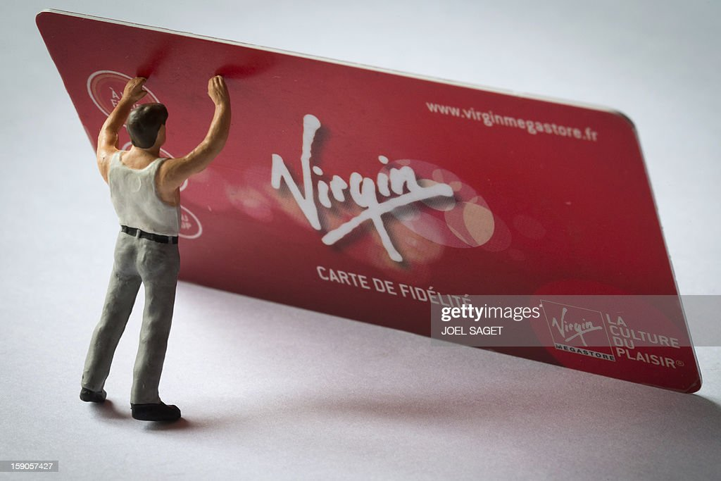 Picture taken on January 7, 2013 in Paris shows an illustration made with a figurine holding a Virgin Megastore loyalty card. The Virgin Megastore chain, which currently employs 1000 workers in France, is planning to file for bankruptcy and is convening an extraordinary board meeting to this effect on January 7.