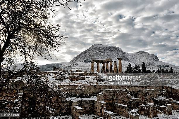 A picture taken on January 8 2017 shows the archaeologicial site of Ancient Corinth with the Temple of Appolon covered by snow in Ancient Corinth...