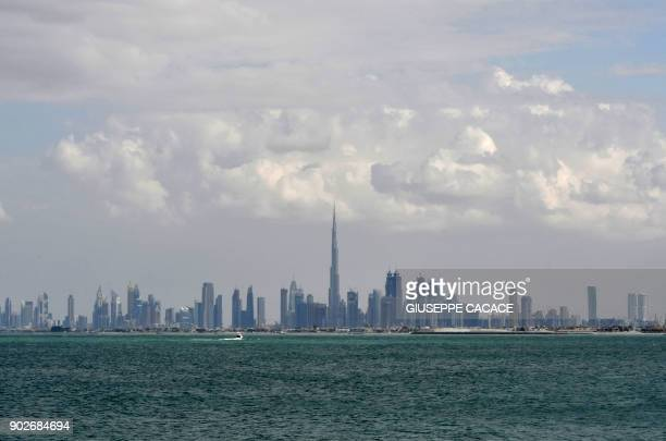 TOPSHOT A picture taken on January 8 2018 shows the skyline of Dubai with the Burj Khalifa in the background / AFP PHOTO / GIUSEPPE CACACE