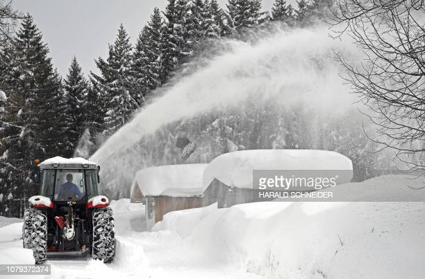 Picture taken on January 8 2019 shows a snow plough clearing the area in Ramsau am Dachstein Austria Up to 15 metres of snow has fallen in central...