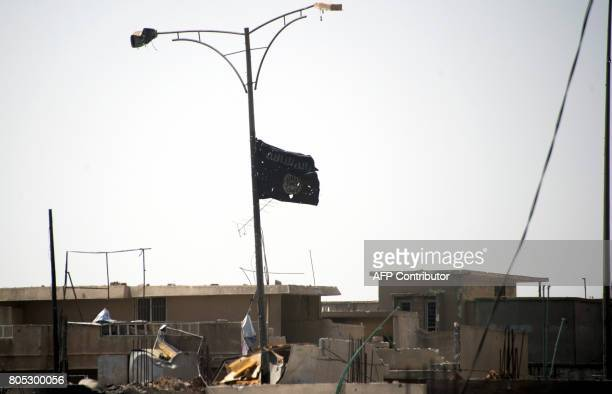 A picture taken on July 1 shows the black flag of the Islamic State group moving in the wind near the medical complex in the Shifa neighbourhood on...