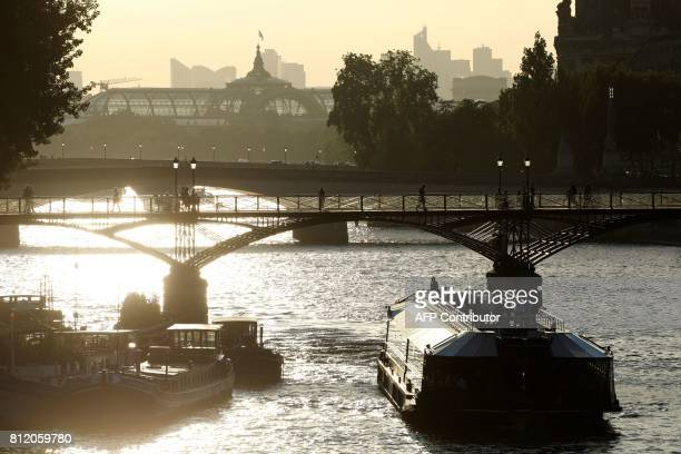 TOPSHOT A picture taken on July 10 2017 shows a bateau mouche tour boat on the Seine river and the glass and steel roof of the Grand Palais from the...