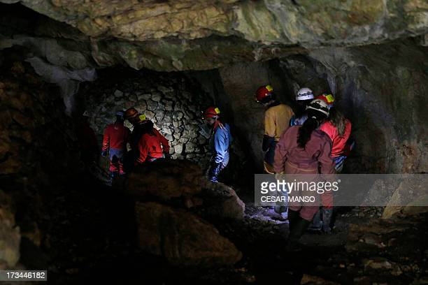 A picture taken on July 11 2013 shows workers excavating the 'Portalon of the Cueva Mayor' the entrance to the main cave of the Gran Dolonia site at...
