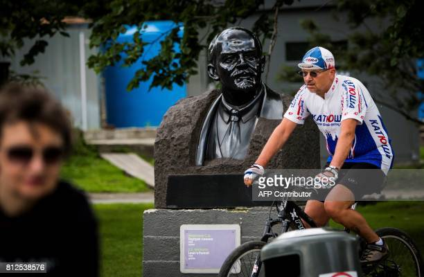 Picture taken on July 11, 2017 shows a cyclist passing by a bust of the founder of the Soviet Union Vladimir Lenin at the Muzeon park of Arts in...