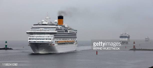 """Picture taken on July 12, 2019 shows the cruise ships """"Aidamar"""" and """"Costa Favolosa"""" entering the channel as they approach Rostock-Warnemuende on the..."""