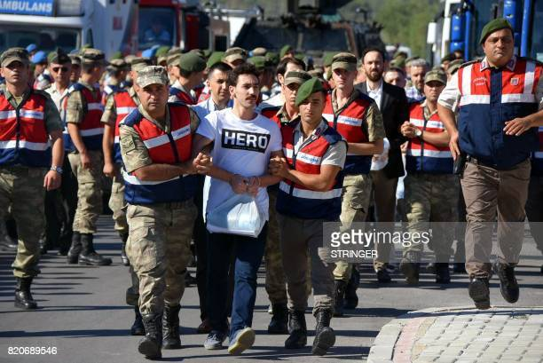 A picture taken on July 13 2017 in Mugla shows Turkish gendarmes escorting a former army special forces officer wearing a tshirt bearing the word...
