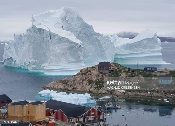 Picture taken on July 13, 2018 shows an iceberg behind houses and buildings after it grounded outside the village of Innarsuit, an island settlement...