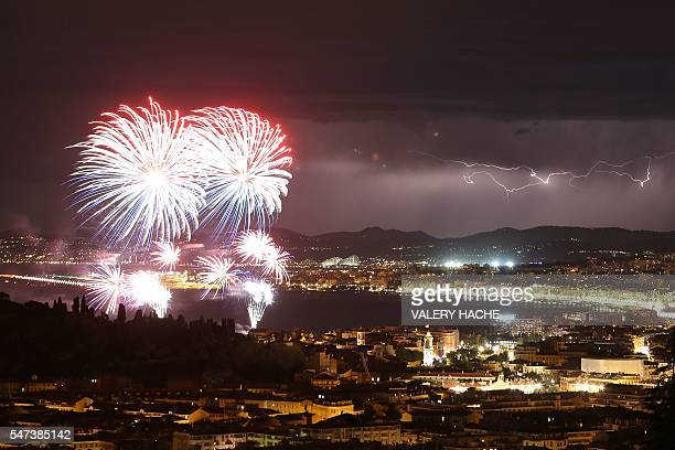 TOPSHOT A picture taken on July 14 2016 shows a flash of lightning as fireworks explode over the French riviera city of Nice southeastern France as...