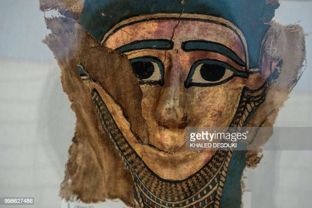 A picture taken on July 14 2018 shows a broken gilded mummy mask on display in front of the step pyramid of Saqqara south of the Egyptian capital...