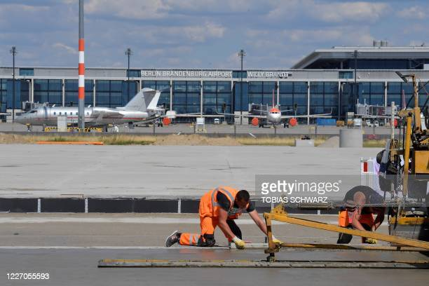 Picture taken on July 14, 2020 shows workers at the Berlin Brandenburg Airport Schoenefeld Airport construction site near Berlin during a press visit...