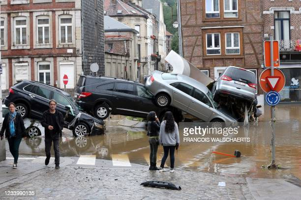 Picture taken on July 15, 2021 shows people passing by cars piled up at a roundabout in the Belgian city of Verviers, after heavy rains and floods...