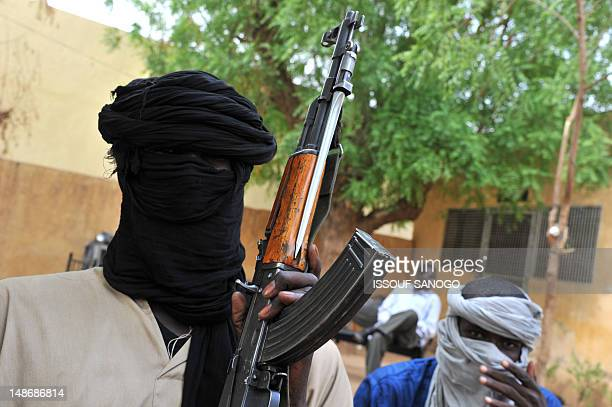 A picture taken on July 16 2012 shows fighters of the Islamist group Movement for Oneness and Jihad in West Africa sitting in the courtyard of the...