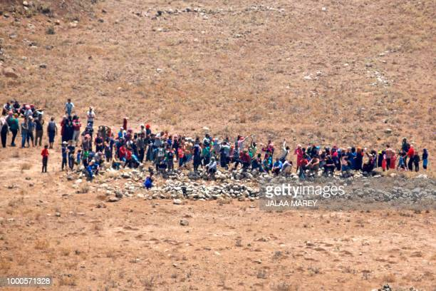 TOPSHOT A picture taken on July 17 2018 from the Israeliannexed Syrian Golan Heights shows refugees coming to fence border between Syria and Israel...