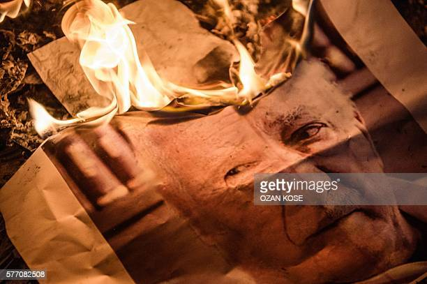 A picture taken on July 18 2016 shows a poster picturing USbased preacher Fethullah Gulen burning during a ProErdogan supporters rally at Taksim...