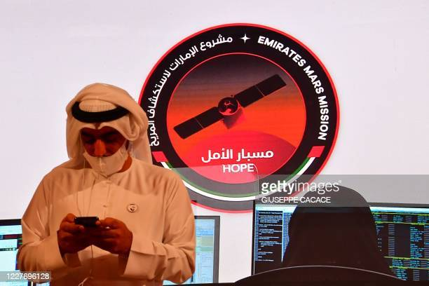 """Picture taken on July 19 shows a man looking at his cellphone during the launch of the """"Hope"""" Mars probe at the Mohammed Bin Rashid Space Centre in..."""