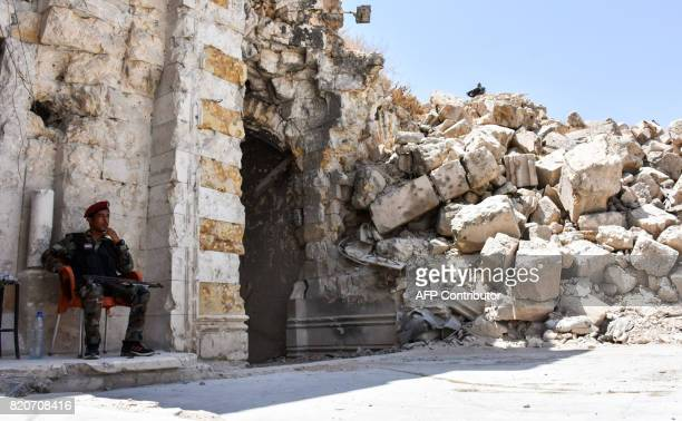 A picture taken on July 22 2017 in the northern Syrian city of Aleppo which was recaptured by government forces in December 2016 shows a member of...