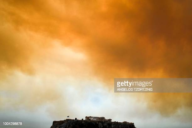 TOPSHOT A picture taken on July 23 2018 shows the Parthenon temple on the Acropolis hill in Athens as smoke billows in background during a wildfire...