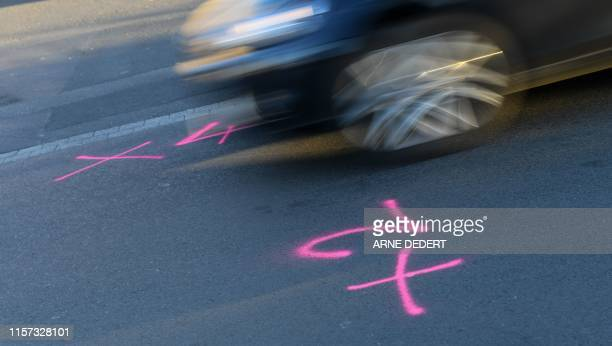 Picture taken on July 23 2019 shows a car driving past marks on the street at the scene of a driveby shooting in Waechtersbach western Germany Police...