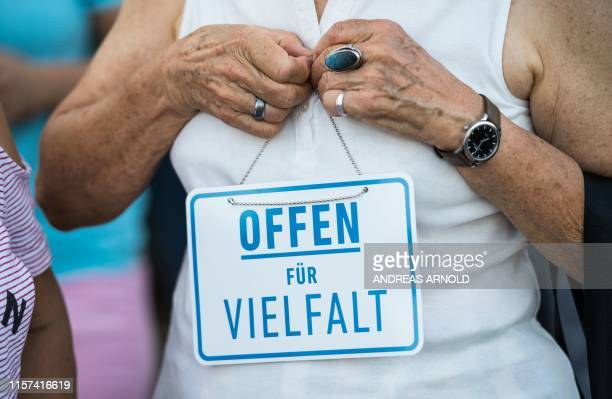 Picture taken on July 23 2019 shows a woman with a sign reading Open for diversity as people protest after a driveby shooting of a 26yearold man from...