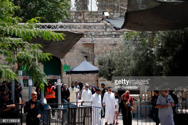 TOPSHOT A picture taken on July 23 shows Muslim tourists walking past Israeli security measures as they exit through Lions' Gate a main entrance to...