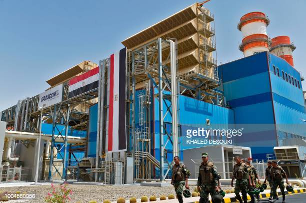 A picture taken on July 24 2018 shows Egyptian soldiers walking in front of a newly constructed combinedcycle power stations on the outskirts of the...