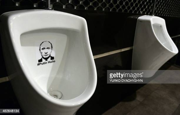 Picture taken on July 25, 2014 shows a sticker bearing a picture of Russian President Vladimir Putin and insulting words on a urinal in the toilet of...