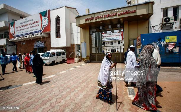 A picture taken on July 25 2017 shows Sudanese men and women walking outside the Radiation and Isotopes Centre Khartoum in the capital Khartoum In...