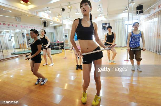 A picture taken on July 26 2010 shows Chinese young women holding batons as they take part in a practice session at a dance centre in Hefei east...
