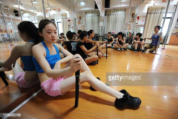 A picture taken on July 26 2010 shows Chinese young women holding batons resting after they take part of a practice session at a dance center in...