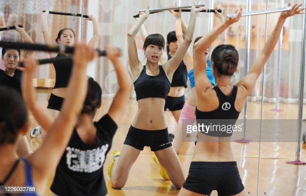 A picture taken on July 26 2010 shows Chinese young women holding up batons as they take part in a practice session at a dance centre in Hefei east...