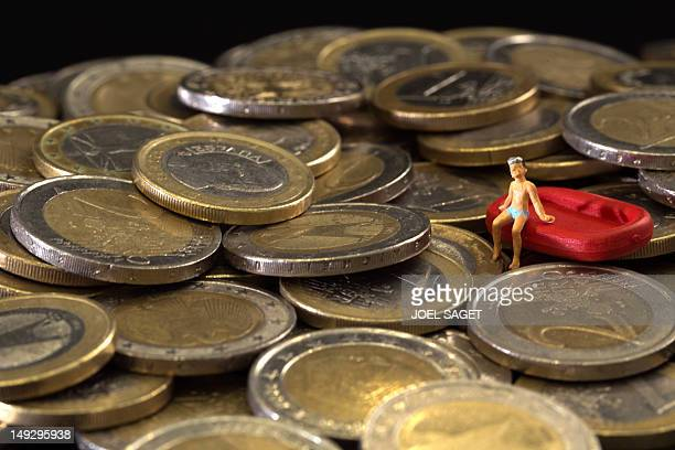 Picture taken on July 26 2012 in Paris shows a figurine and euro coins to illustrate the cost of the holydays AFP PHOTO/JOEL SAGET