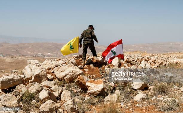 A picture taken on July 26 2017 during a tour guided by the Lebanese Shiite Hezbollah movement shows a fighter from the group placing a flag of the...