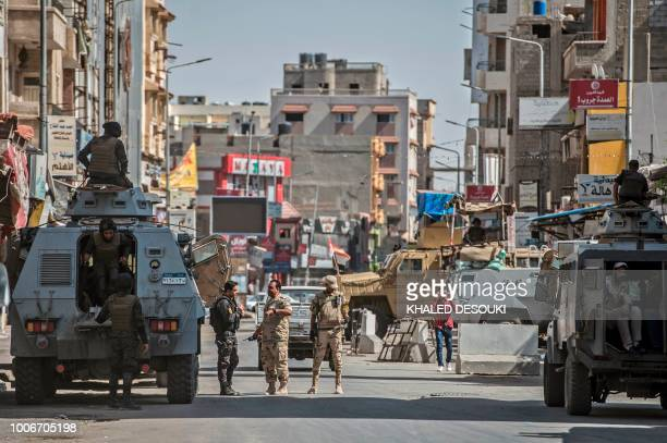 A picture taken on July 26 2018 shows Egyptian policemen stand guarding a street in the North Sinai provincial capital of ElArish With fruit and...
