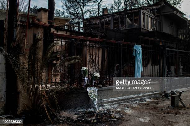 A picture taken on July 26 2018 shows flowers on a fence of a house where two bodies where found following a wildfire at the village of Mati near...