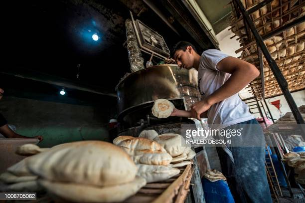Picture taken on July 26 during an army-organised tour, shows an Egyptian baker working at his shop in el-Arish city in the northern Sinai Peninsula....
