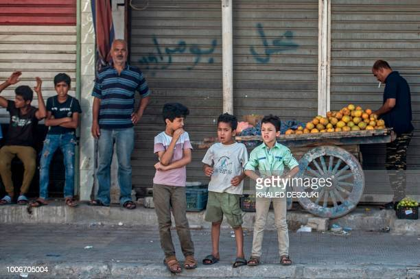 Picture taken on July 26 during an army-organised tour, shows Egyptian kids standing in a street in el-Arish city in the northern Sinai Peninsula. -...