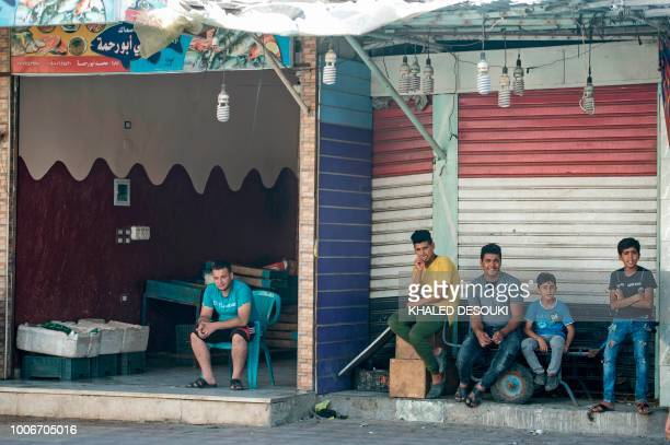 Picture taken on July 26 during an army-organised tour, shows Egyptian youths sitting in a street in el-Arish city in the northern Sinai Peninsula. -...