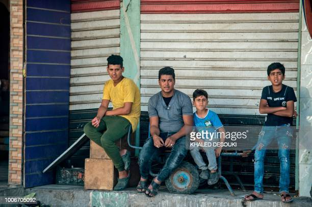 Picture taken on July 26 during an army-organised tour, shows Egyptians youth sitting in a street in el-Arish city in the northern Sinai Peninsula. -...