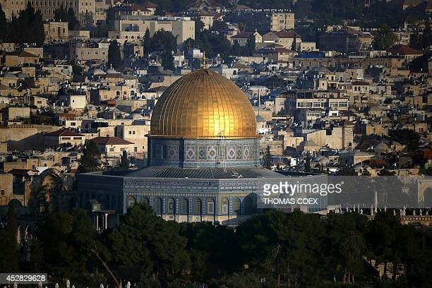 A picture taken on July 28 2014 shows the Dome of the Rock shining at sunrise on the first day of Eid alFitr holiday that marks the end of the holy...