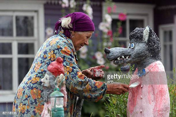 Picture taken on July 29 2008 shows Belarus Maria Fanko painting a cement sculpture of a wolf outside her house 200 km from Minsk in Meretskiye The...