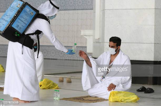 A picture taken on July 29 2020 shows a pilgrim receiving water at the Grand Mosque complex in the holy city of Mecca at the start of the annual...